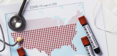 Coronvirus specimen sit on top of a map of the United States with a stethoscope and glasses.