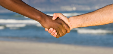 Two people of different skin colors, shake hands.