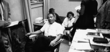 Martin Luther King Jr sits in a room with others.