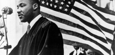 Dr. Martin Luther King Jr. with the American flag behind him.