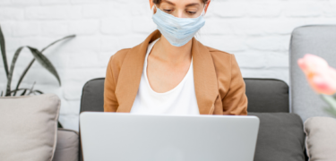 A woman on her laptop with a mask on.