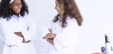 Two women stand together in lab coats.