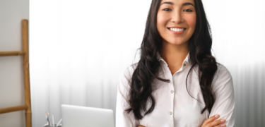 A professional woman crossing her arms and smiling in front of a work desk.