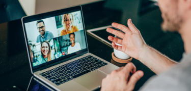 A person speaks with co-workers over a video call.