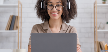 A woman with headphones smiles at her laptop.