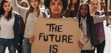 "A woman stands in front of many other women holding a sign saying, ""The Future is Female."""