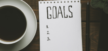 """Coffee sits next to a notepad with """"goals"""" written."""