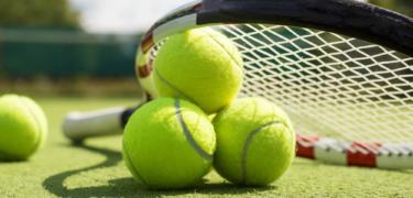 A tennis racket with tennis balls.
