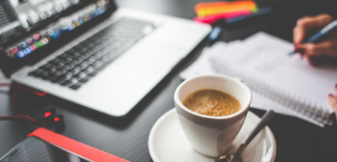 A latte sits in front of a laptop with a notebook.